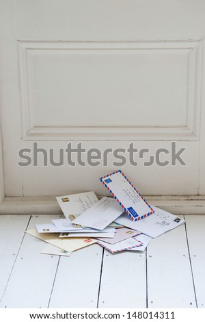 Letters on floorboards at front door - stock photo
