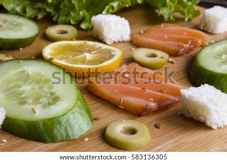 Lettuce, chopped salmon, cucumber, slices of lemon, olives, baguette, topped with sesame seeds on kitchen board close up. Healthy organic food.