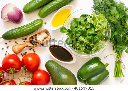 Lettuce, corn salad, tomatoes, cucumbers, green peppers, avocado, onion, parsley, dill, olive oil and vinegar, salt and pepper on a white background. Vegetable salad ingredients. Horizontal. Top view. - stock photo