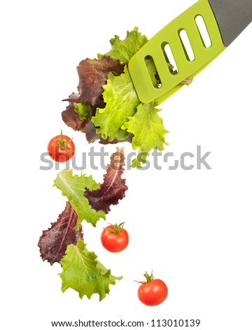 Lettuce leaves in salad tongs with falling tomatoes - stock photo