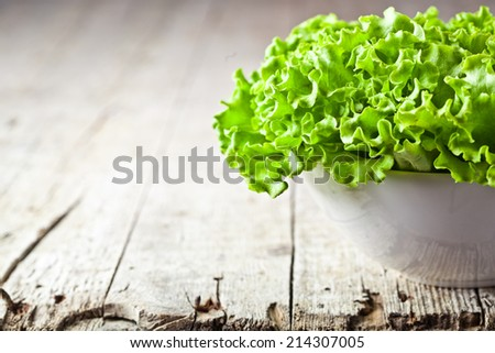 lettuce salad in a bowl closeup on rustic wooden table - stock photo