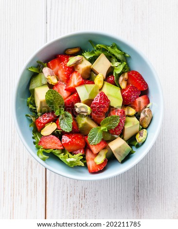Lettuce salad with avocado and strawberry in blue bowl - stock photo
