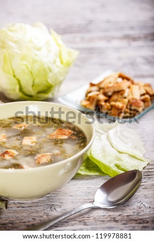Lettuce soup on old wooden table