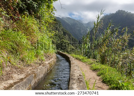 Levada, irrigation canal with hiking path through the mountains at Madeira Island, Portugal - stock photo