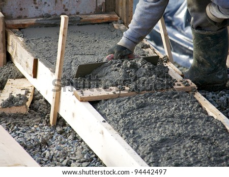 Levelling concrete footings for the foundation of a house under construction - stock photo