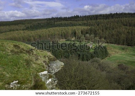 Levisham, Yorkshire, UK. Farmhouse and surrounding fields in the middle of the North York Moors National Park with pine woodland and rolling landscape in spring, Levisham, Yorkshire, UK. - stock photo