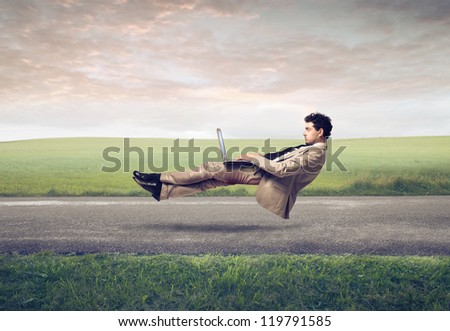 Levitating businessman, on a road, using a laptop computer - stock photo