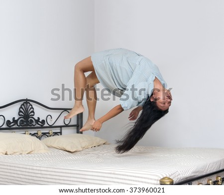 Levitating girl sleeping over the bed. Woman in a nightgown hangs over the bunk. Obsession of demon hells. Paranormal sleep at home. - stock photo