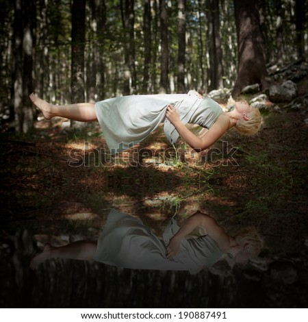 Levitating woman in the forest above water - stock photo