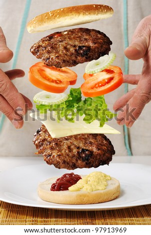 Levitating zero gravity burger in hands - stock photo