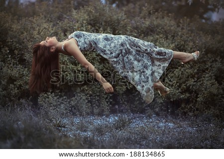 Levitation girl on a bed in a sweet dream. - stock photo