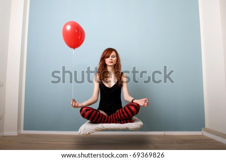 Levitation portrait of beautiful red caucasian girl with heart balloon. - stock photo