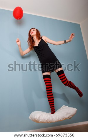 Levitation portrait of beautiful redhead caucasian girl with heart balloon. - stock photo