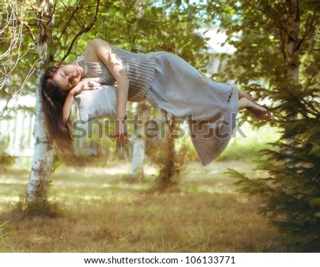 levitation, the sleeping girl in the woods - stock photo