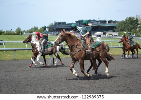 LEXINGTON, KY - AUGUST 10: Jockies warming up their horses before a race at Keeneland Horse Racing Track on August 10, 2011 in Lexington, Kentucky. - stock photo