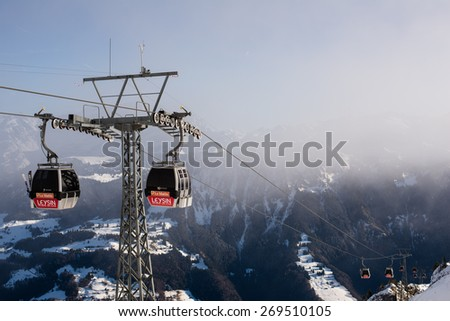 LEYSIN, SWITZERLAND - 29 DECEMBER 2013 : Two cable car on the front side and a plurality of cable cars in the far and view to mountains in the resort town on Leysin in the Swiss Alps. - stock photo