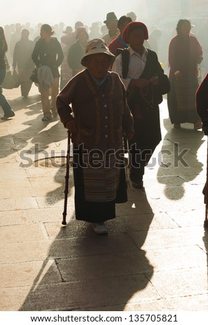 LHASA, CHINA - OCTOBER 17: An unidentified mature Tibetan pilgrim woman walks around the smoky Jokhang temple, a famous tourist, pilgrimage site in Tibet on October 17, 2007 in Lhasa, China - stock photo