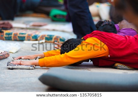 LHASA, CHINA - OCTOBER 17: An unidentified Tibetan prostrator lies flat on stomach with oustretched arms at Jokhang temple, a famous pilgrimage site in Tibet on October 17, 2007 in Lhasa, China - stock photo