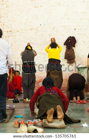 LHASA, CHINA - OCTOBER 17: Unidentified women with bound legs prostrate towards the Jokhang temple wall, Barkhor, a famous tourist, pilgrimage site in Tibet on October 17, 2007 in Lhasa, China - stock photo