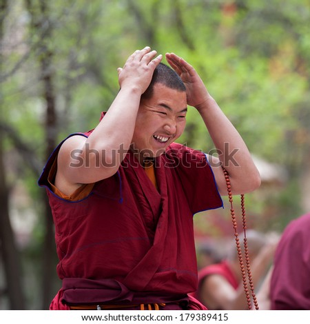 LHASA - MAY 1: Unidentified monk breaks out in laughs during a debate held at Sera monastery on May 1, 2013 in Lhasa, Tibet. Debating is part of the monastery curriculum to become a higher lama.
