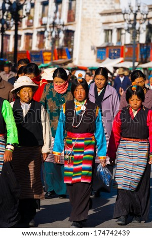 Lhasa, Tibet, China - October 18, 2007: Group of traditionally dressed Tibetan women in colorful aprons, headpieces walking, circumambulating around the Barkhor and Jokhang temple