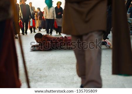 Lhasa, Tibet, China - October 17, 2007: Tibetan pilgrim man prostrating sideways, perpendicular to foot traffic direction around Jokhang temple, Barkhor, a famous pilgrimage site  - stock photo