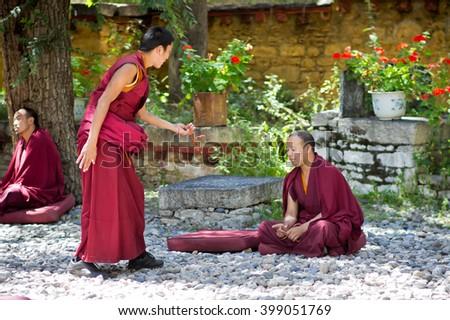 LHASA/TIBET - SEPTEMBER 10, 2011: Two tibetan monks debate in the famous Drepung monastery during traditional monks debates in Lhasa, Tibet A.R. of China - stock photo