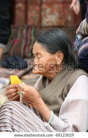 LHASA, TIBET - SEPTEMBER 25: unidentified pilgrim woman reads prayer flag to show her piety to Buddha and meditate on the threshold of the Jokhang Temple on September 25, 2009 in Lhasa, Tibet, China - stock photo