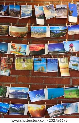 LI JIANG, CHINA - AUGUST 26: Some colorful Li Jiang landscape postcards are hanging on a bar's wall on August 26 in Li Jiang, China. - stock photo