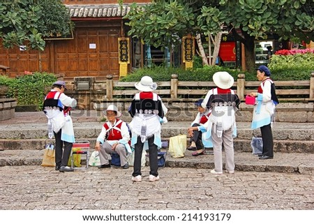 LI JIANG, CHINA - AUGUST 26: Some Lijiang local women are on their traditional nation costumes preparing their own dances at a small square on August 26 in Li Jiang, China. - stock photo