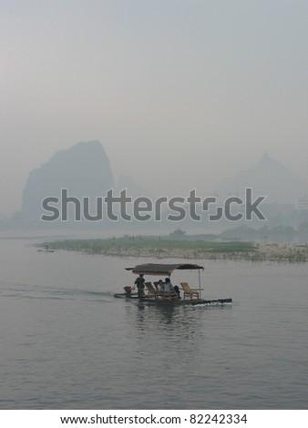Li Jiang River cruise in fog - stock photo
