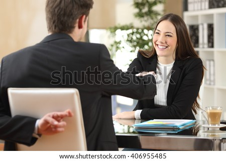 Liar businessman closing a deal and crossing fingers back at office - stock photo