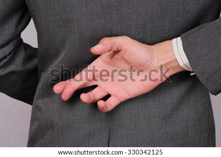 Liar businessman with crossed fingers at back . Ethics concept. Unfair business practices - stock photo