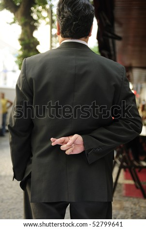 liar: businessman with fingers crossed behind his back - stock photo