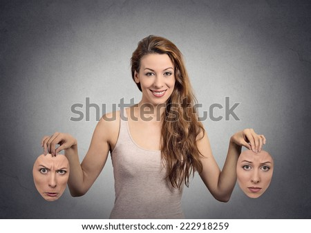 Liar. Portrait beautiful happy girl holds two masks isolated grey wall background. Human face expressions, emotions, feelings, bipolar state of mind concept - stock photo