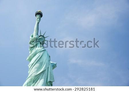Liberty Statue, a landmark of new york city, with blue sky - stock photo