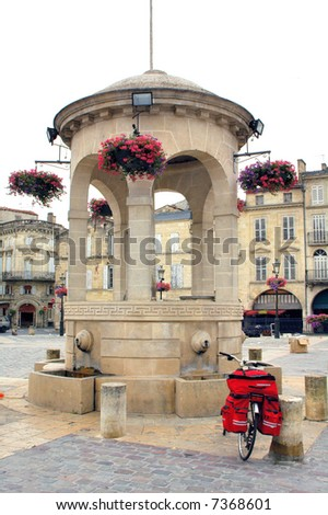 Libourne (Bordeaux, Aquitaine, France) - Fountain and bicycle with red bags - stock photo