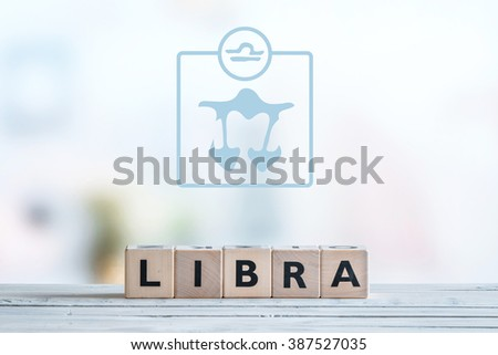 Libra star sign on a wooden table - stock photo