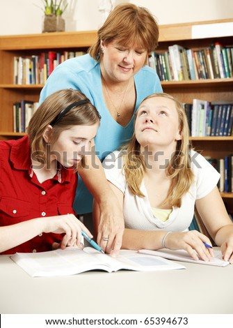 Librarian assisting two teenage students with their research. - stock photo