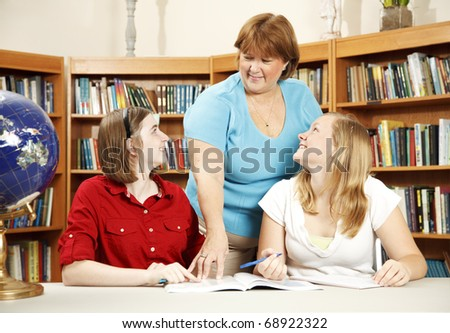 Librarian helps too teenage students in the school library.