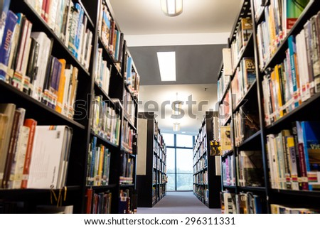 Library book shelf aisles with focus on the far end bright window with greenery  - stock photo
