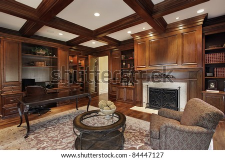 Library in luxury home with marble fireplace