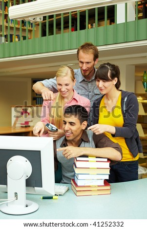 Library staff pointing at monitor on counter