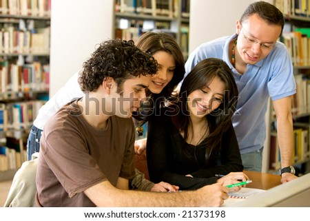 library students smiling and doing group coursework - stock photo