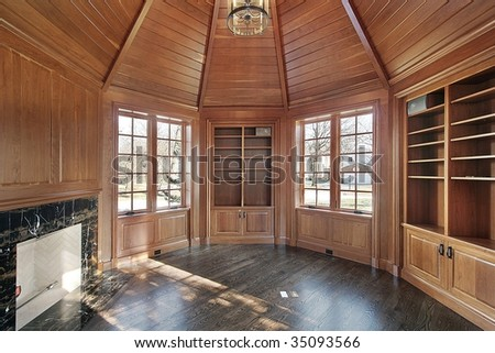 Library with wood paneled walls and fireplace - stock photo