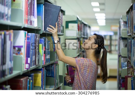 Library ,women student find book for study. - stock photo