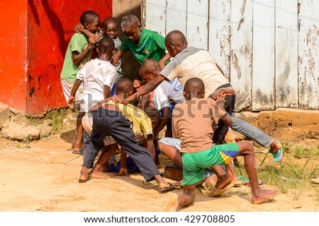 LIBREVILLE, GABON - MAR 6, 2013: Unidentified Gabonese children play and fight together outside in the yard in Gabon. People of Gabon suffer of poverty due to the unstable economical situation