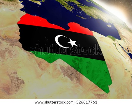 Libya with embedded flag on planet surface during sunrise. 3D illustration with highly detailed realistic planet surface and visible city lights. Elements of this image furnished by NASA.