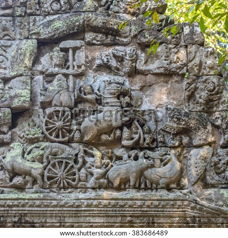 Lichen covered broken bas relief in a wall showing carts, soldiers, animals and birds, Preah Khan, the Temple of the Sacred Sword,  built by Jayavarman VII  AD1191, Cambodia - stock photo