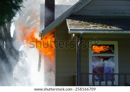 Licks of flame burst out of the window of a house surrounded by thick black smoke - stock photo